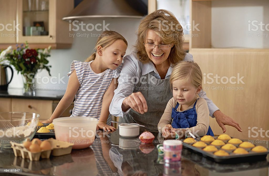 Demonstrating the art of decorating cupcakes Two little girls baking cupcakes with the help of their grandmother at home 4-5 Years Stock Photo