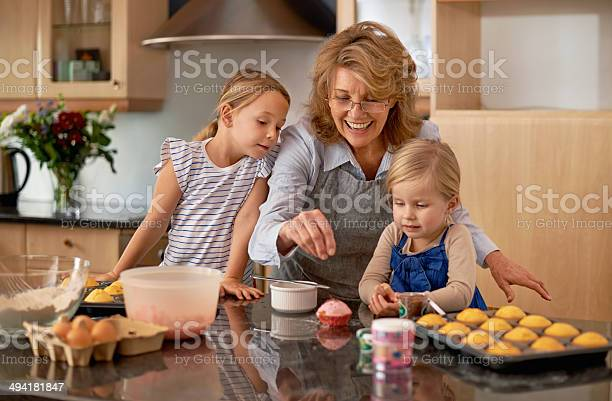 Demonstrating The Art Of Decorating Cupcakes Stock Photo - Download Image Now