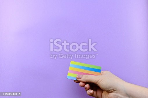 844190384 istock photo Demonstration of a multi-colored striped card in a hand on a purple background. 1190866315