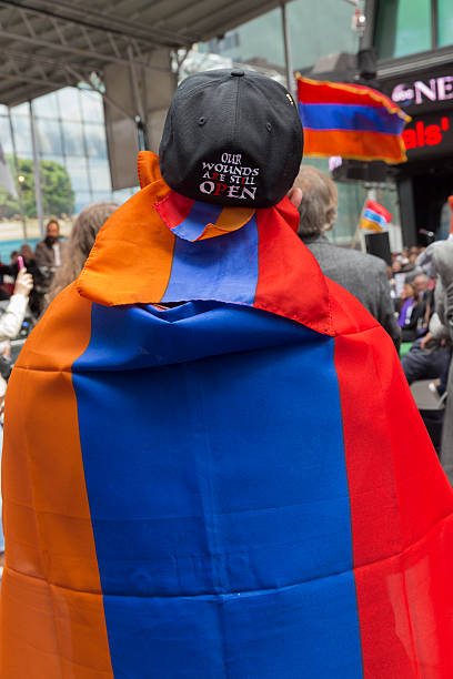 Demonstration New York, NY USA - April 26, 2015: Man wrapped into Armenian flag at rally in Manhattan Times Square to mark centennial of the deaths of 1.5 million Armenians under the Ottoman Empire in 1915 armenian genocide stock pictures, royalty-free photos & images