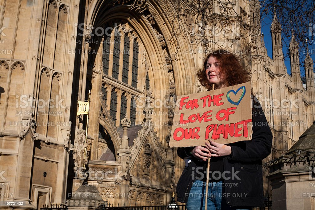 Demonstrator for climate change action holds placard outside UK Parliament stock photo