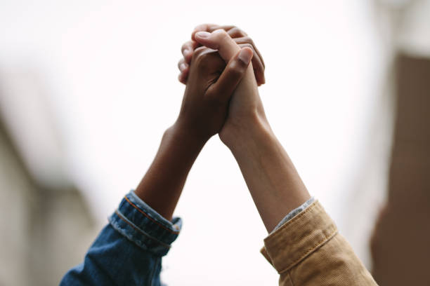 Demonstrators protesting together holding hands stock photo