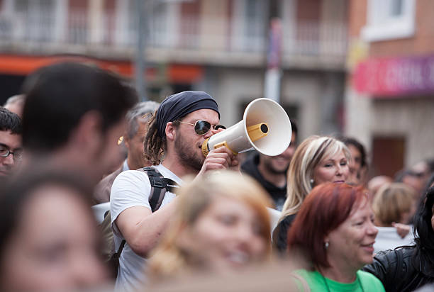 demostrator with megaphone protesting against austerity cuts Badajoz, Spain - March 29, 2012: young demonstrator with megaphone protesting against austerity cuts, March against the Labor Reform approved by the Government of Spain on March 2012 labor union stock pictures, royalty-free photos & images
