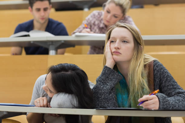 Demotivated students in a lecture hall stock photo