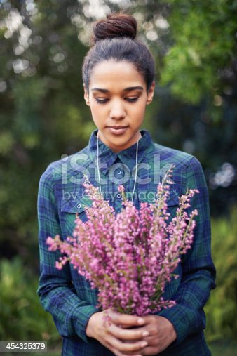 A young woman holding a bunch of flowers in a garden