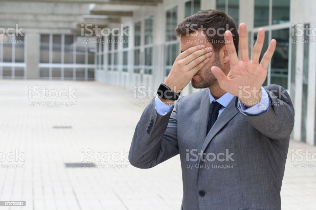 Denial concept with businessman covering his eyes stock photo