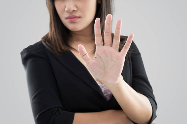 Denial Business woman in black suit showing her denial with no on her hand against gray background forbidden stock pictures, royalty-free photos & images