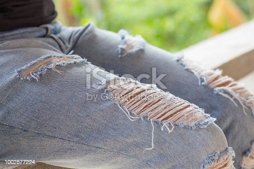 istock Denim blue fabric frame. Washed denim fabric with fringe edge on bleached denim background, 1002577224