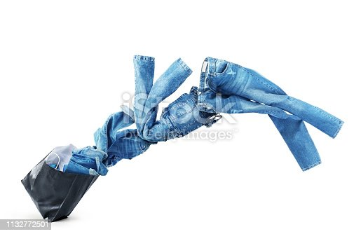istock Denim clothes flying out of a black bag isolated on white background. Sale. 1132772501
