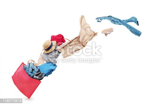 istock Denim clothes flying out of a black bag isolated on white background. Sale. 1132772513