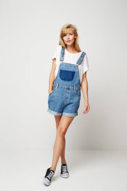 Denim dungaree woman Denim dungaree woman posing for camera, portrait shorts stock pictures, royalty-free photos & images
