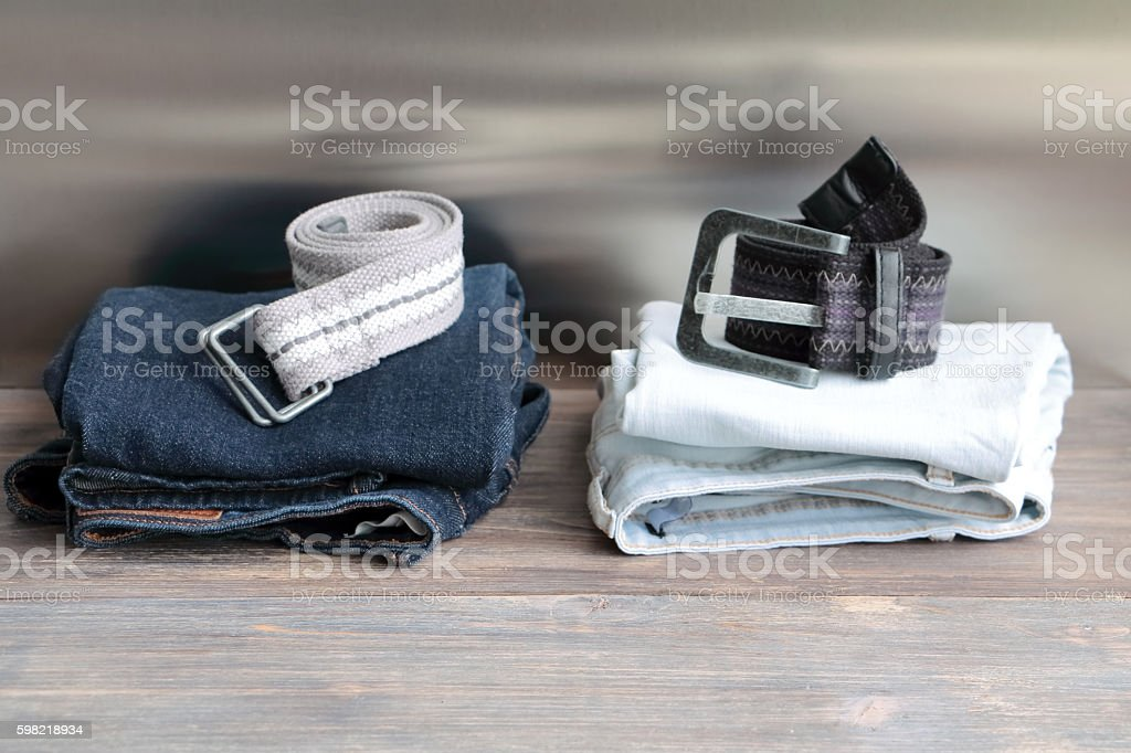 Denim jeans with belts stacked on a wooden board. foto royalty-free