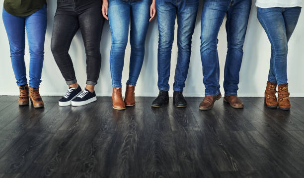 Denim - let's get back to basics Cropped shot of a group of unrecognizable people wearing jeans while standing in a row styles stock pictures, royalty-free photos & images