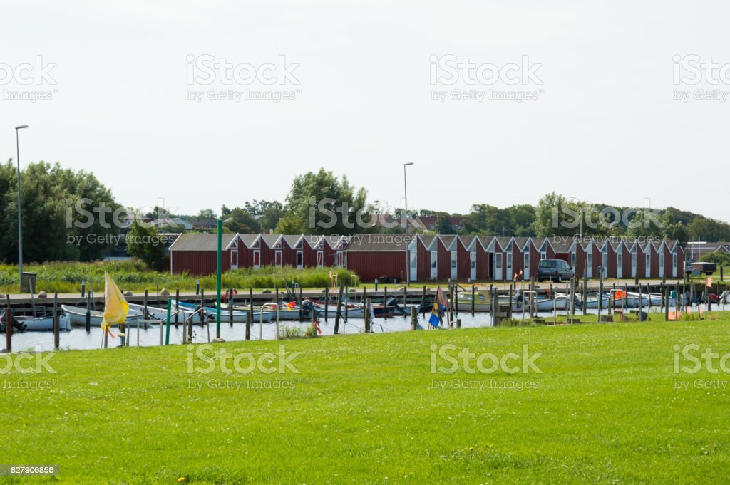 Denmark, Northern Jutland, Nibe. The towns marina/harbor with typical red wooden danish buildings and ships. stock photo