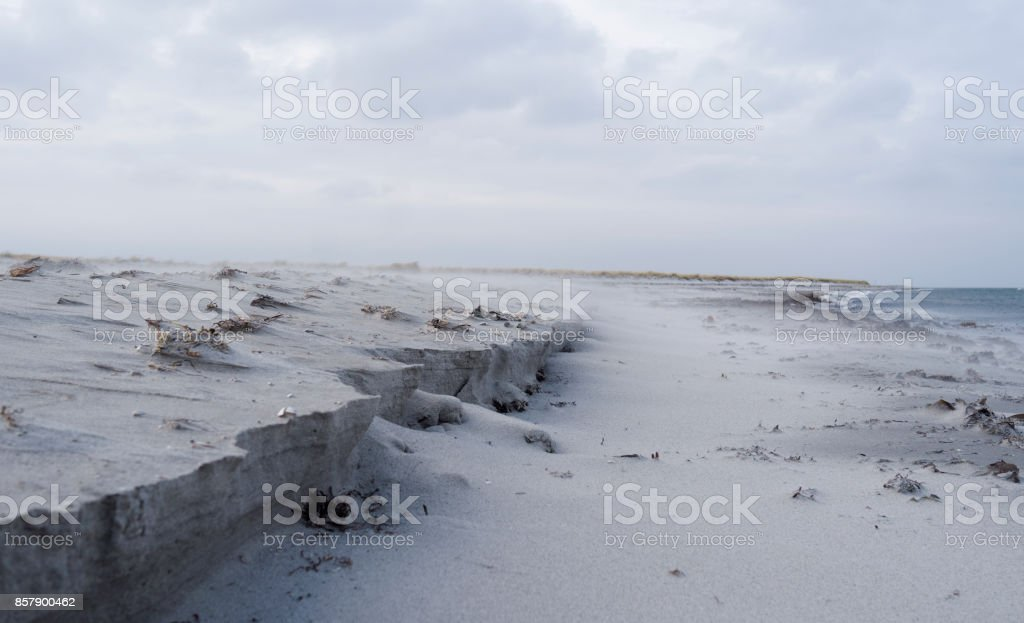Denmark: The strong April wind in North Jutland is blowing the fine sand grains from the dunes over the beach to the sea stock photo