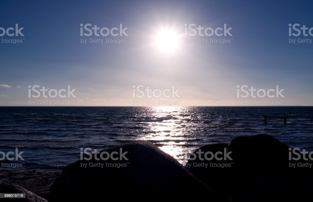 Denmark: View from a harbor mole in North Jutland to the evening sun reflecting in the sea stock photo