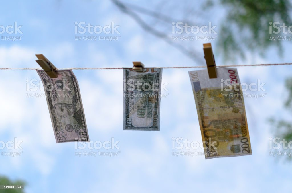 Denominations of dollars and euros on a cord on pegs. stock photo