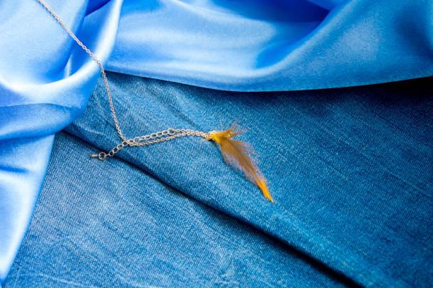 dichten blauen denim-stoff, glatte himmelblaue seide und gold kette mit anhänger feder - goldgefüllte kette stock-fotos und bilder