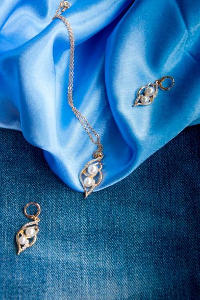 dichten blauen denim-stoff, glatte himmelblaue seide, gold kette und ohrringe mit weißen perlen mit glänzenden zirkonia steinen eingelegt - goldgefüllte kette stock-fotos und bilder