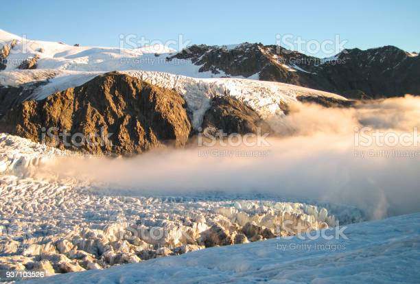 Photo of Dense Clouds Cover the Fox Glacier at Sunset in New Zealand