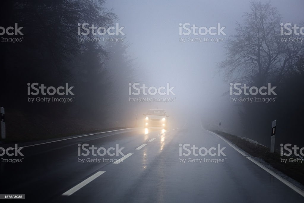 Dense fog on the country road, oncoming traffic royalty-free stock photo
