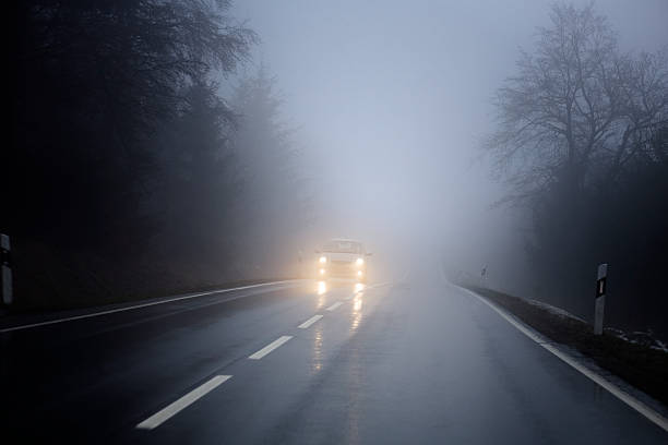 dense fog on the country road, oncoming traffic - mist donker auto stockfoto's en -beelden