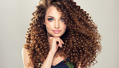 Soft smile on the face of flawless young girl, vivid makeup and dense, curly hairstyle. Voluminous, spring-like,elastic curls in a hairstyle of young, pretty model.