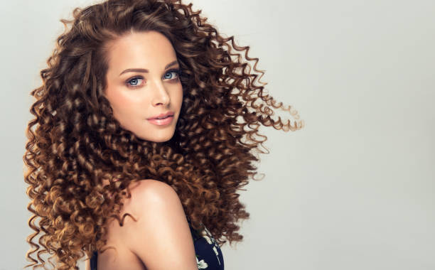dense, spring-like,elastic curls in a hairstyle of young, pretty model. frizzy hair. - permanente foto e immagini stock