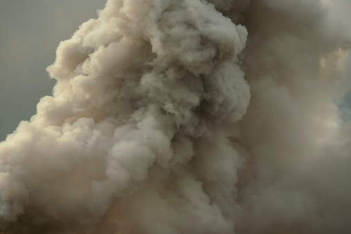 Dense white smoke rising from the raging wildfire,smoke background,close up swirling white smoke background.