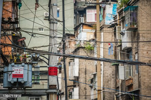 Yichang, China - August 2019 : Densely wired telephone and electric cables outside residential buildings in Yichang town