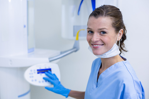 istock Dental assistant adjusting x-ray equipment 651773172
