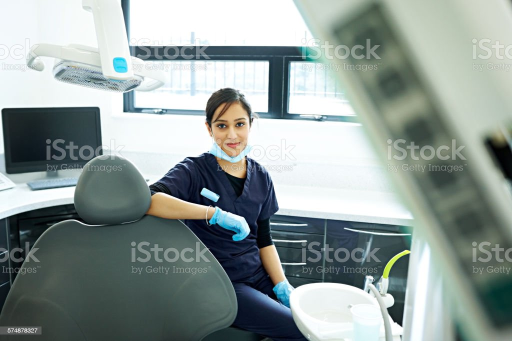 Dental assistant sitting on a dentist stool stock photo