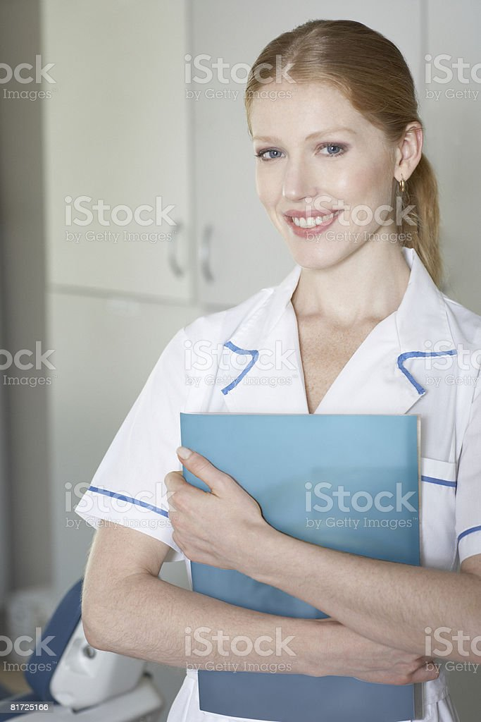 Dental assistant standing in examination room holding clipboard and smiling royalty-free stock photo
