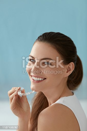 Dental care. Smiling woman with white smile using whitening tray. Portrait of girl with healthy teeth using invisible braces aligner, orthodontic silicone trainer for dental correction