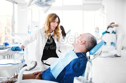Adult male patient listening solutions that his dentist is presenting for his dental health issues.