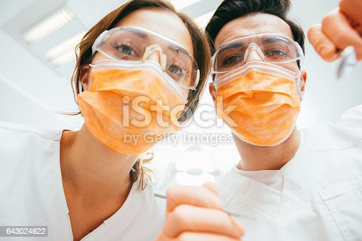 Dentists working on patient's teeth.
