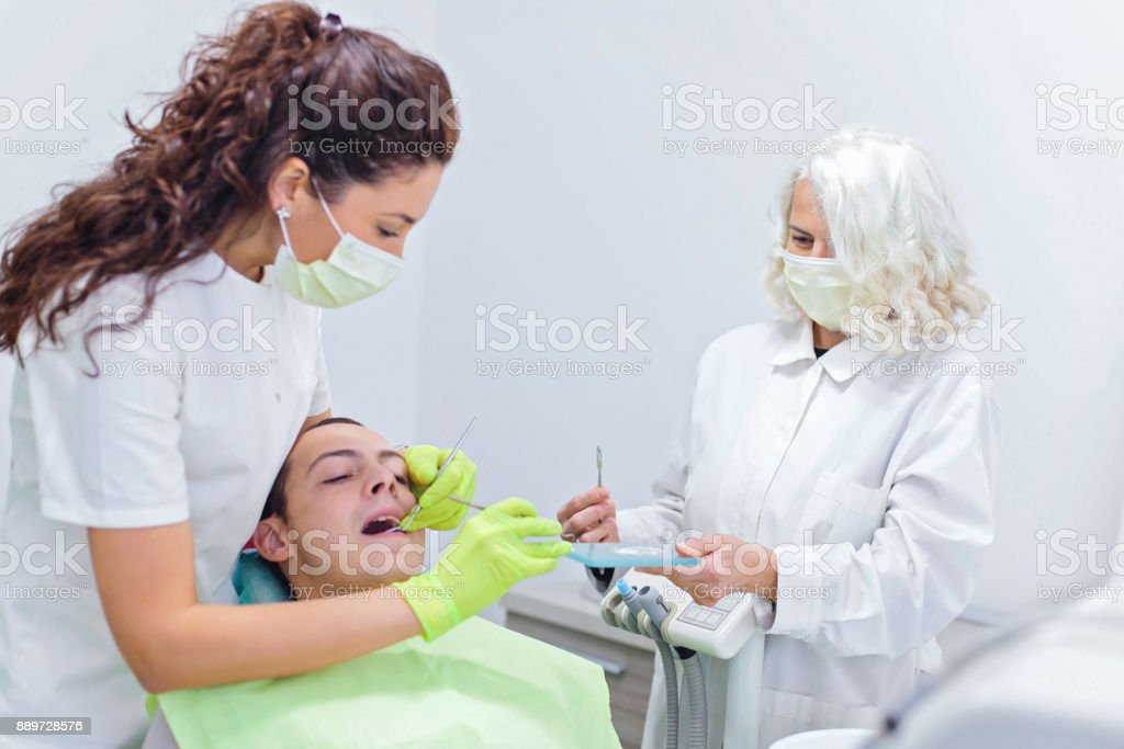 Man having her teeth examined at dentist office. Female dentist and...