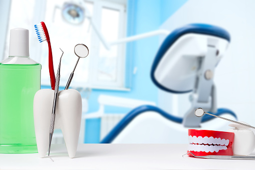 Dental health and teethcare concept. Dental mirror with explorer probe and toothbrush in white tooth model near mouthwash. Human jaw model with dental floss against dental office and chair background