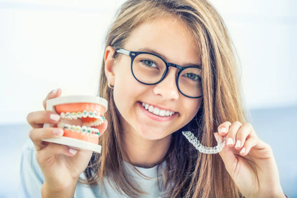 Dental invisible braces or silicone trainer in the hands of a young smiling girl. Orthodontic concept - Invisalign. stock photo