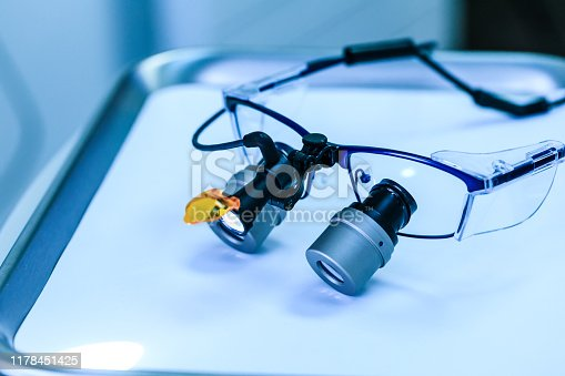 Dental medical glasses with binocular lenses, in dentistry clinic. Dentist glasses or dental optic on a real medical laboratory. Modern technology equipment in background of surgery room.