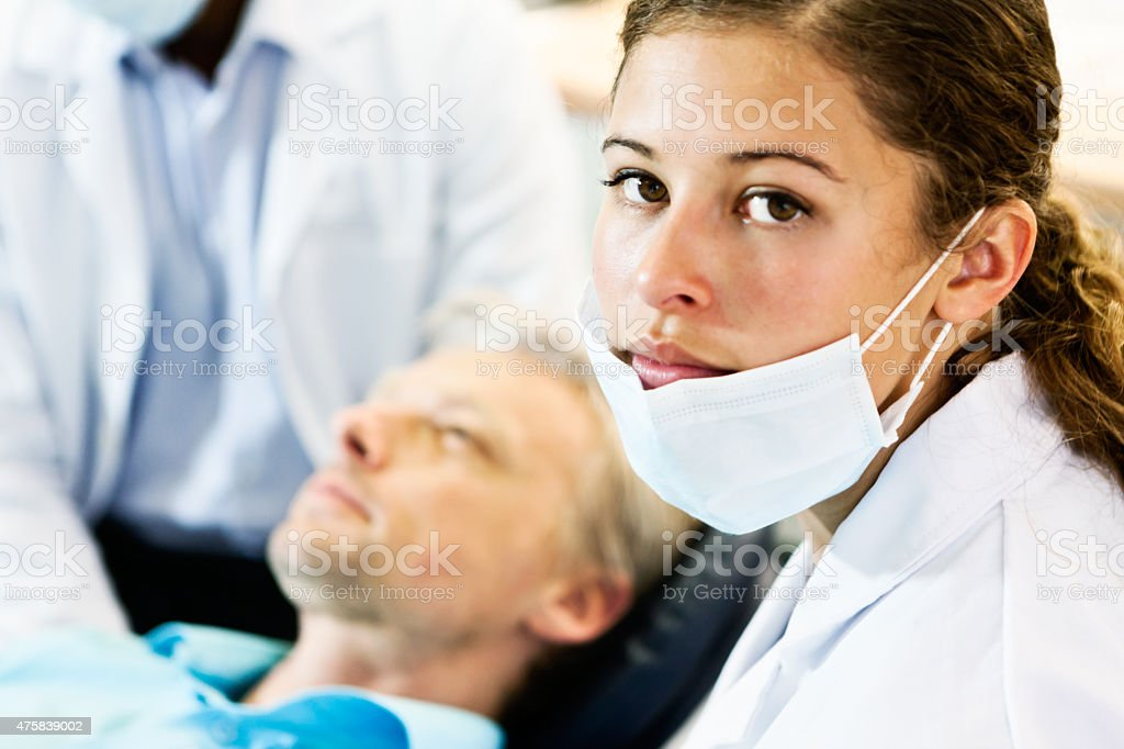 Dental nurse looks round from dentist and male patient stock photo