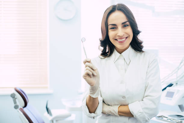 Dental Professional. Assure and beautiful dental doctor with a dentist mirror in her hand and brilliant healthy smile all over her face in front of dentist room dentist stock pictures, royalty-free photos & images