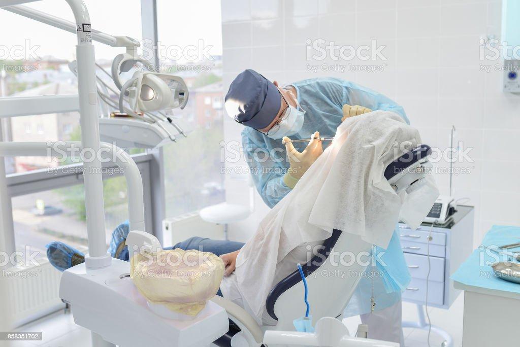 Operación de cirugía dental en la clínica del dentista moderno, cirujano haciendo la inyección al paciente - foto de stock