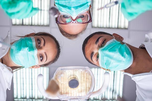 dental team arbeiten mit einem patienten arbeiten in schützende kleidung - sprechstundenhilfe stock-fotos und bilder