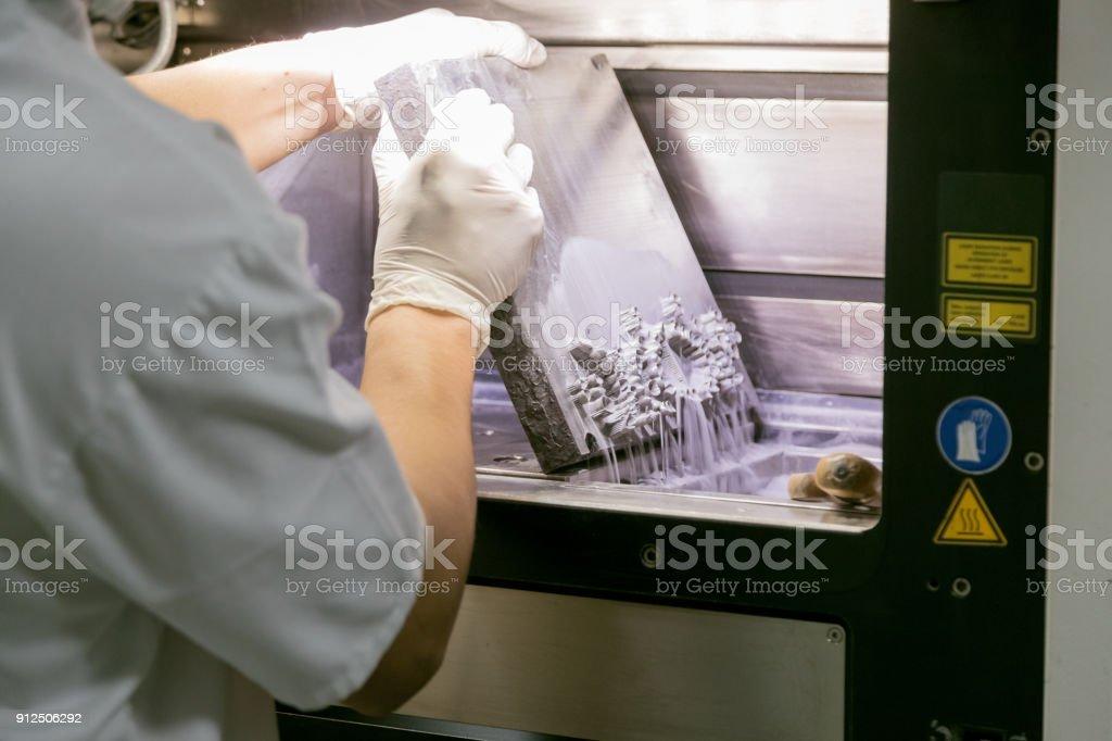 Dental technician taking dentures out of 3D powder printer stock photo