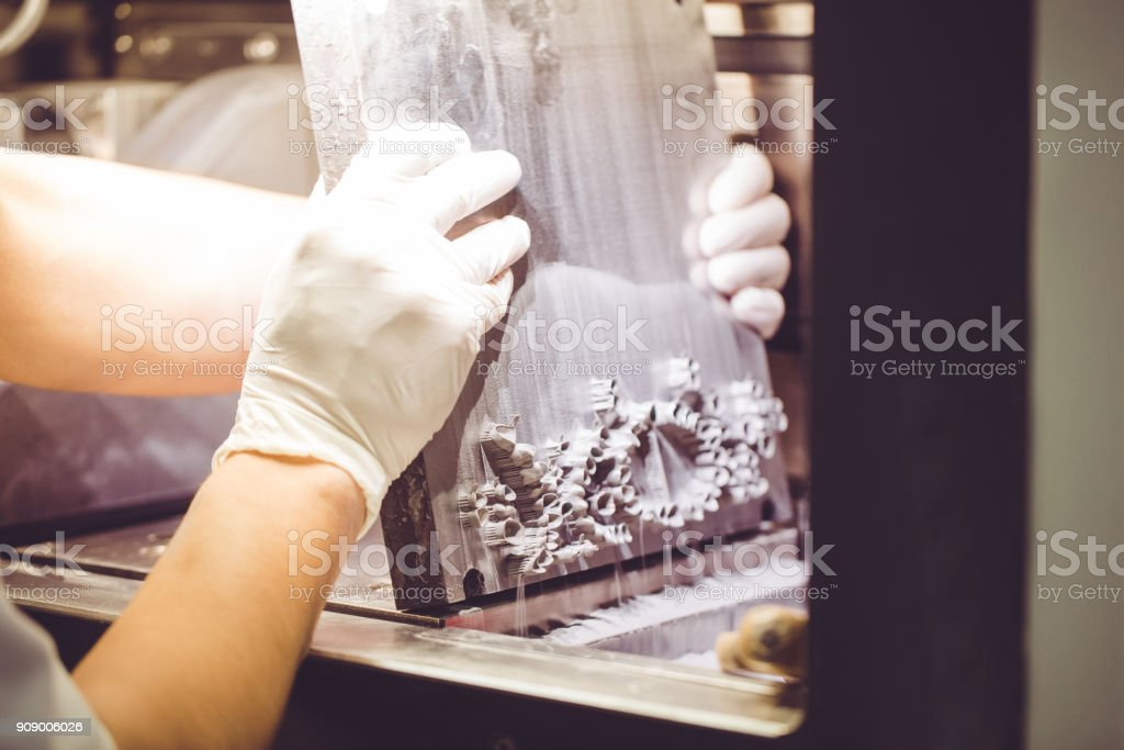 Dental technician taking out denture from 3D powder printer stock photo