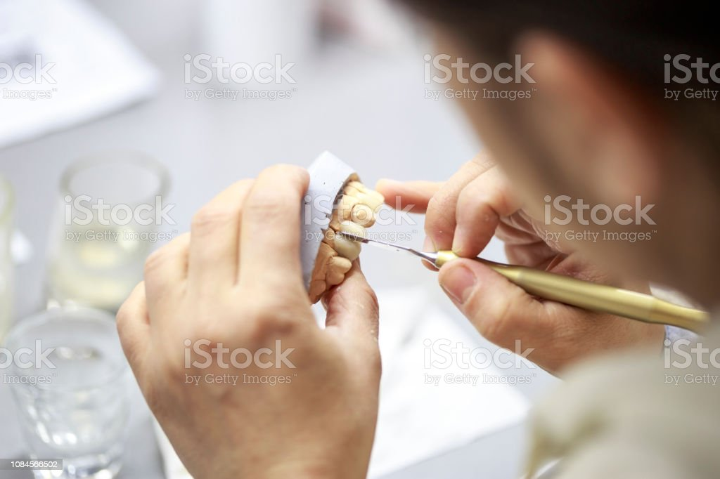 Dental technician working on a dental casting. - Royalty-free Accuracy Stock Photo