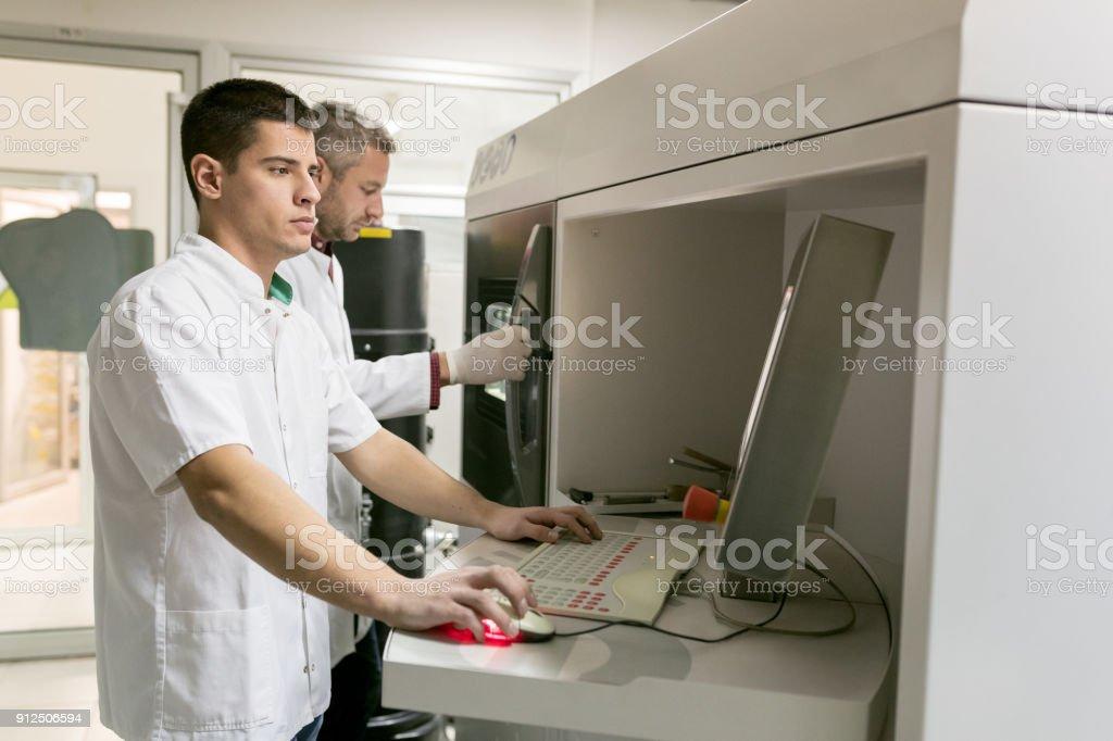 Dental technicians at work, setting metal 3D powder printer stock photo