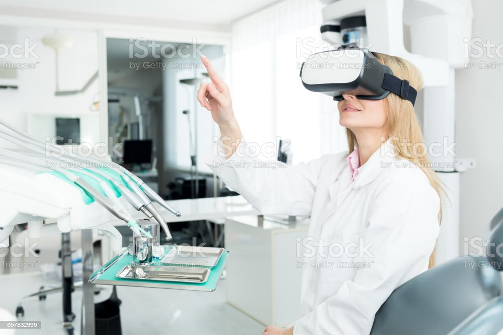 Dental worker touch screen & using Vr headset stock photo