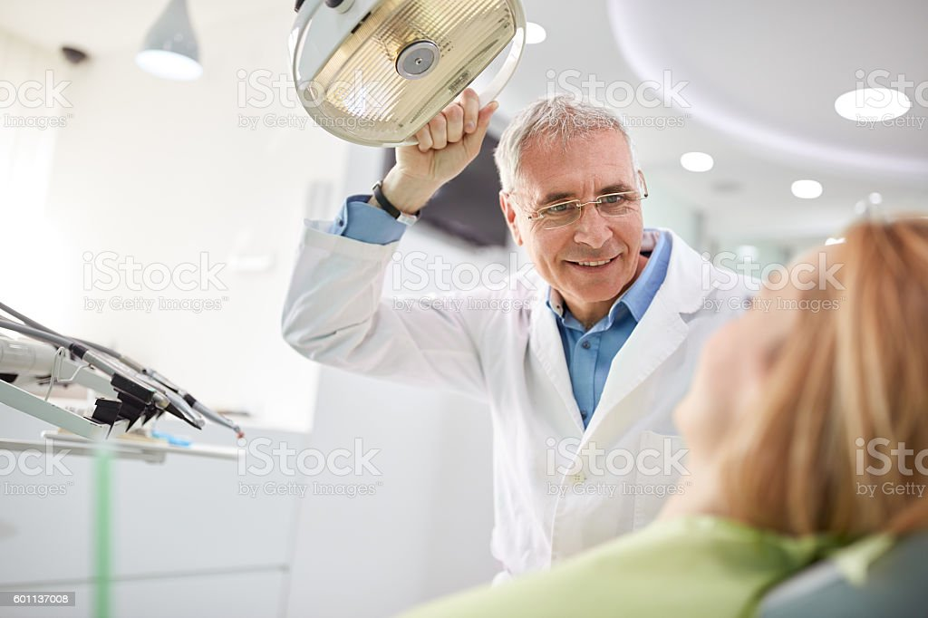 Dentist adjust searchlight before starting work - foto de stock